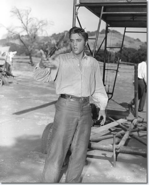 Elvis plays around with a prop knife during the filming of 'Love Me Tender'. From the book, Inside Love Me Tender.