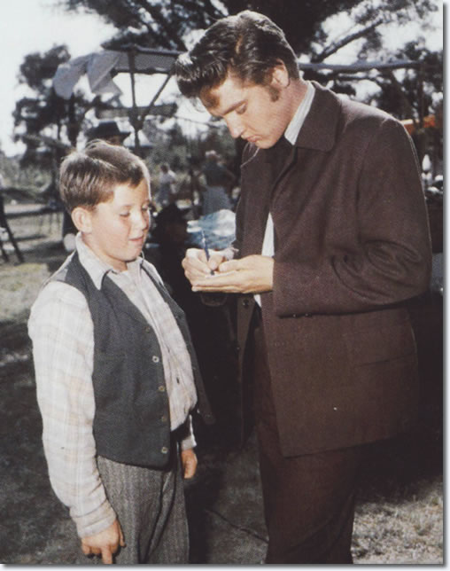 Elvis signs an autograph on the set of 'Love Me Tender'. From the book, Inside Love Me Tender