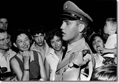 Elvis explains the insignia on his uniform to fans at the gates of Graceland Sunday evening June 1, 1958.