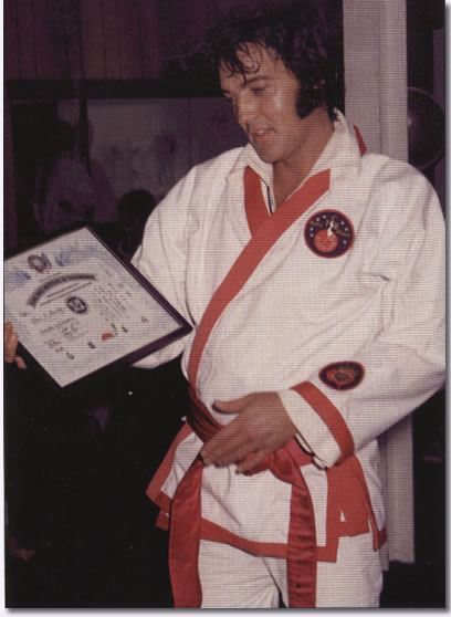 Elvis Presley with certificate for his honorary 8th degree black belt from Kang Rhee