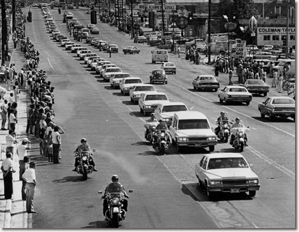 A string of white Cadillacs follow the hearse carrying the body of rock 'n' roll musician Elvis Presley along Elvis Presley Boulevard on the way to Forest Hills Cemetery in Memphis, Tenn., Aug. 19, 1977.