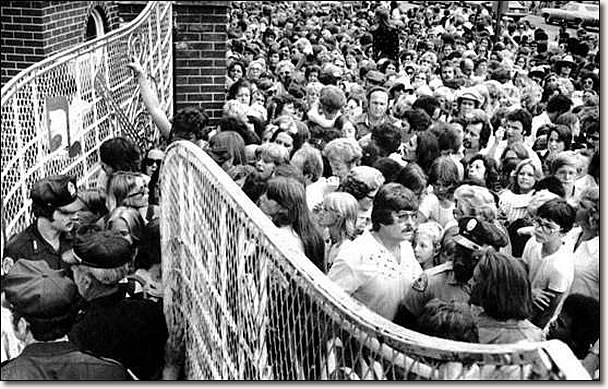 A crowd pushes toward the gates of Graceland Mansion in Memphis, to view the body of Elvis Presley