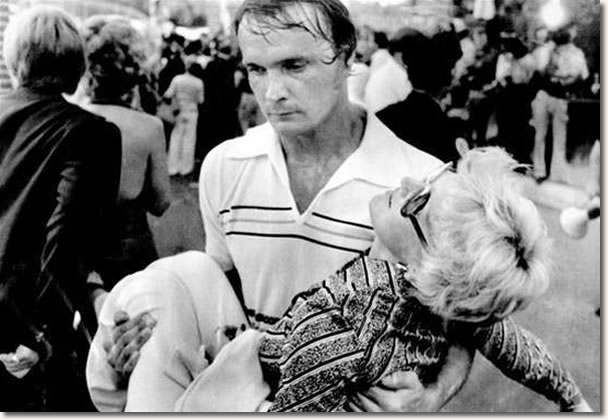 An exhausted volunteer carries a victim of the heat and confusion to a first aid station inside the gates of Graceland Mansion in Memphis, where thousands gathered for a chance to view Elvis Presley's body.