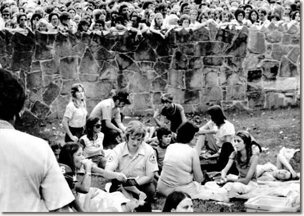 Members of the Shelby County emergency squad treat some of the hundreds of fans who became ill while waiting for a chance to get a glimpse of the body of Elvis Presley at the Graceland Mansion in Memphis.