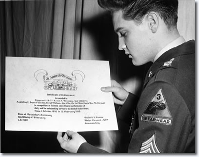 Elvis Presley holding the certificate of achievement that the Army presented to him upon his honorable discharge in February of 1960.