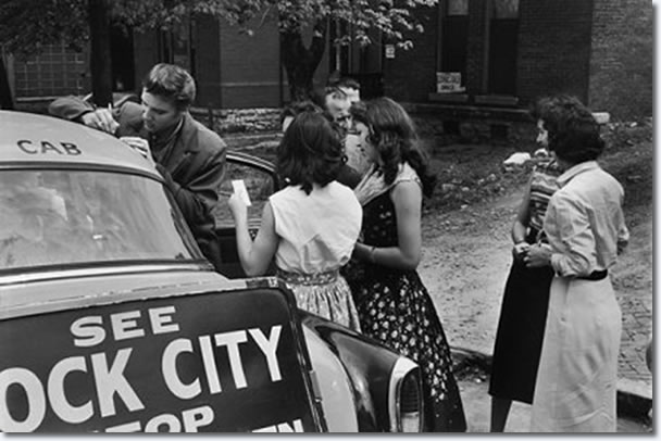 Elvis signing autographs for fans as he leaves the studio - April 14, 1956