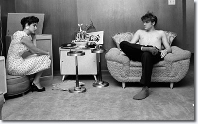 After having taken a shower, and still bare chested, Elvis has his high school sweetheart, Barbara Hearn, listen on the phonograph to the acetate disc with cuts of his songs from the New York recording session. 1034 Audubon Drive, Memphis, Tenn. July 4, 1956. (Photo © Alfred Wertheimer. All rights reserved.)