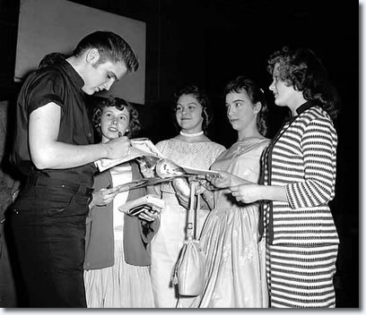 Elvis Presley signed autographs for four remarkably composed fans at the St. Paul, Minnesota Auditorium.