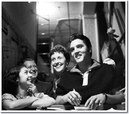 Elvis signs some autographs with British comedienne Joyce Grenfell seen in the background.