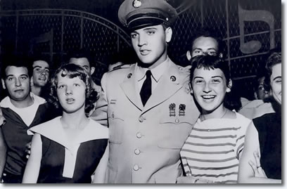 Jo Ann Mullins (Left) and Tudy Harrison (Right) greet singer Elvis Presley at the gate to his home. Presley made his first public appearance here since he started a two-week furlough on completion of basic training in the Army.