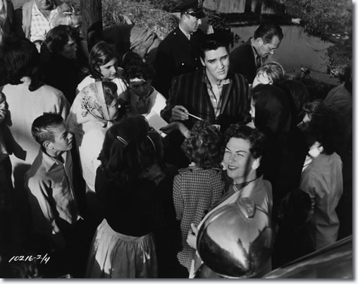 Elvis on location at Lake Pontchartrain Shack, New Orleans March 4,1958. Elvis signs some autographs for waiting fans. Elvis is wearing a shirt not seen in the movie, so he is either arriving or departing the location.