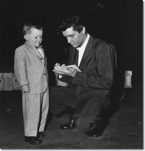 A young fan on the paramount set gets an autograph from Elvis,who is signing his name on the single release of Teddy Bear. Tuesday February 4, 1958.