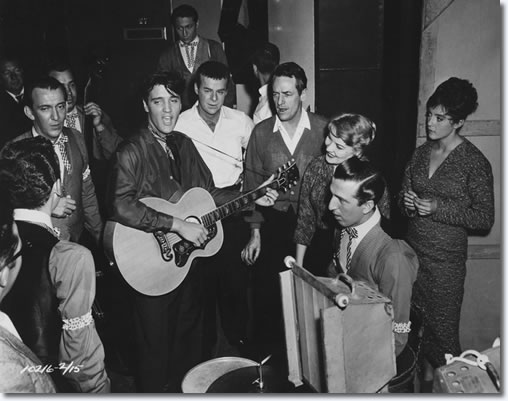 Hoyt Hawkins with (back to camera) takes part in a music number backstage with, Hugh Jarrett, Bill Black (holding upright bass), Elvis Presley, Scotty Moore at the top of picture, Ric Roman next to Elvis, Charles O'Curren, Patti Page, D.J. Fontana sat with his drum kit, and Liliane Montevecchi (Nina).