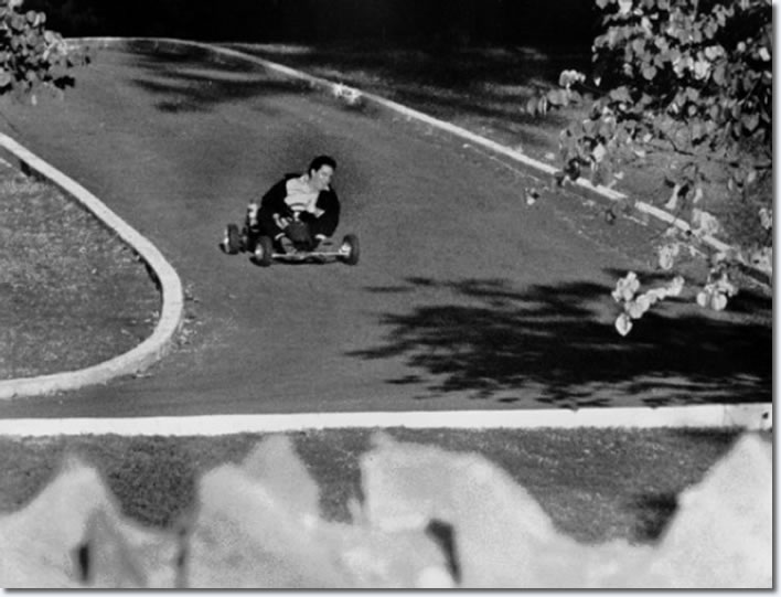 Elvis Presley on a go cart racing up the driveway of Graceland : October 12, 1965