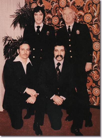 Elvis in Denver Police uniform with (standing right) Denver Police Captain Jerry Kennedy and (kneeling, left to right) officers Bob Cantwell and Ron Pietrafeso, January 1976.