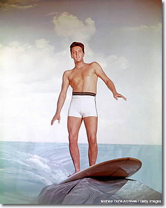 April 1961: This picture totally illustrates his unfortunate movie career. I especially love the fake rock that's holding the surfboard. The whole thing exemplifies his Hollywood years. This was a Paramount [Studios] giveaway -- they sent out 8x10 color positives to the newspapers, which is very unusual.