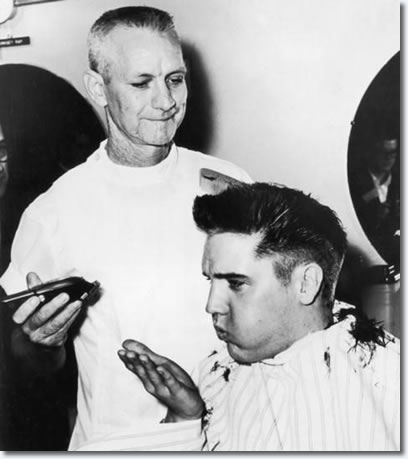 Elvis Presley blows a strand of hair from his hand, while receiving a haircut from a US Army barber, Fort Chaffee, Arkansas.