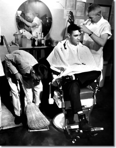 Elvis Presley receiving a haircut from a US Army barber, Fort Chaffee, Arkansas.