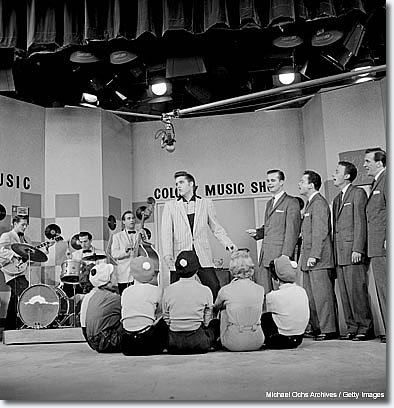 June 1956: This is also an Earl Leaf shot. It's the only time I have ever seen Elvis with his trio -- Scotty, Bill and D.J. -- and the Jordanaires all in the same shot. To me, that's just totally unique. And then you throw in the general feel of the extras -- the girls sitting there -- and the fake Colony Music Shop background. But the key thing is that I've never seen all of them together in one picture.