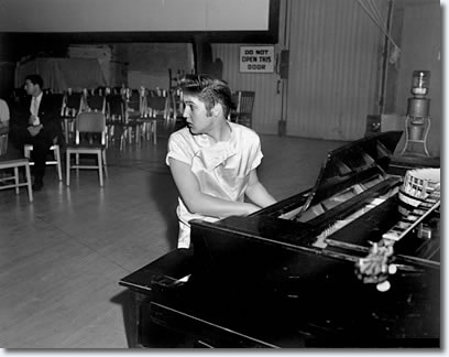 August 1956: This is during 'Love Me Tender' -- this is Elvis the first time he ever recorded without his usual musicians. He's at the 20th Century Fox soundstage studio. There's the novelty of him playing piano, which one seldom sees. Here he is in a whole new milieu -- he's in L.A. There's an openness and yet a startledness and a freshness about this shot.