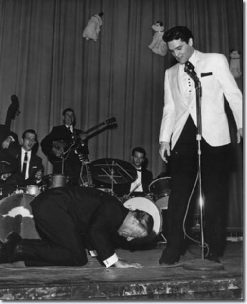 Comedian George Jessel hit the stage in an exaggerated salaam to the King of rock and roll.