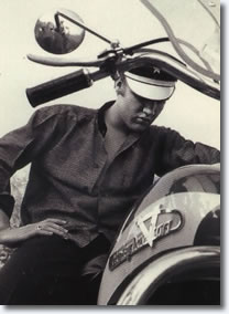 Elvis wearing a cool motorcycle cap and sitting on his Harley Davidson